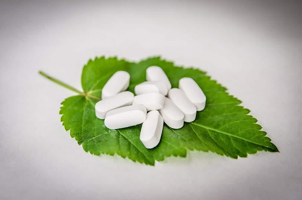 White pills on green leaf