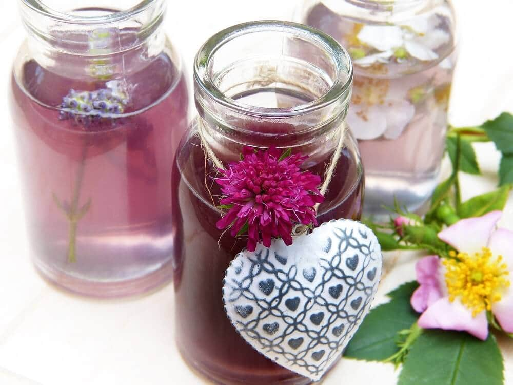 Three different types of essential oils with flowers