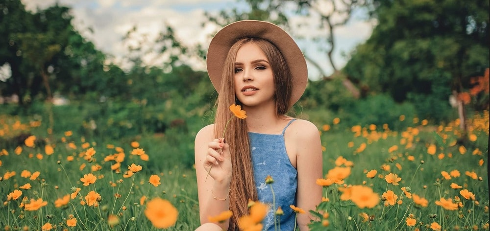 woman with beautiful healthy skin sitting on a filed with flowers