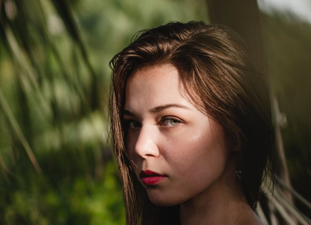 Beautiful girl with clear skin on green forest background